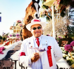 "Tournament of Roses volunteer, or ""white suiter"", at the City of Downey float, Home for the Holidays"